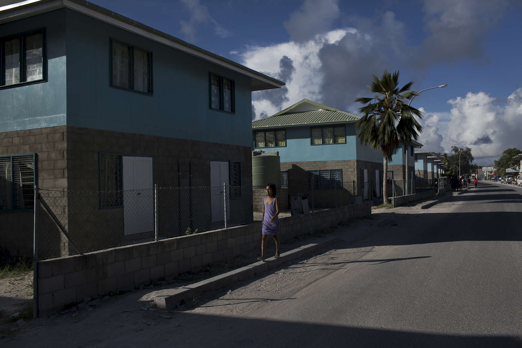 A young girl walks past recently built houses in Betio which is the largest township of Kiribati's capital city, South Tarawa, and the country's main port.