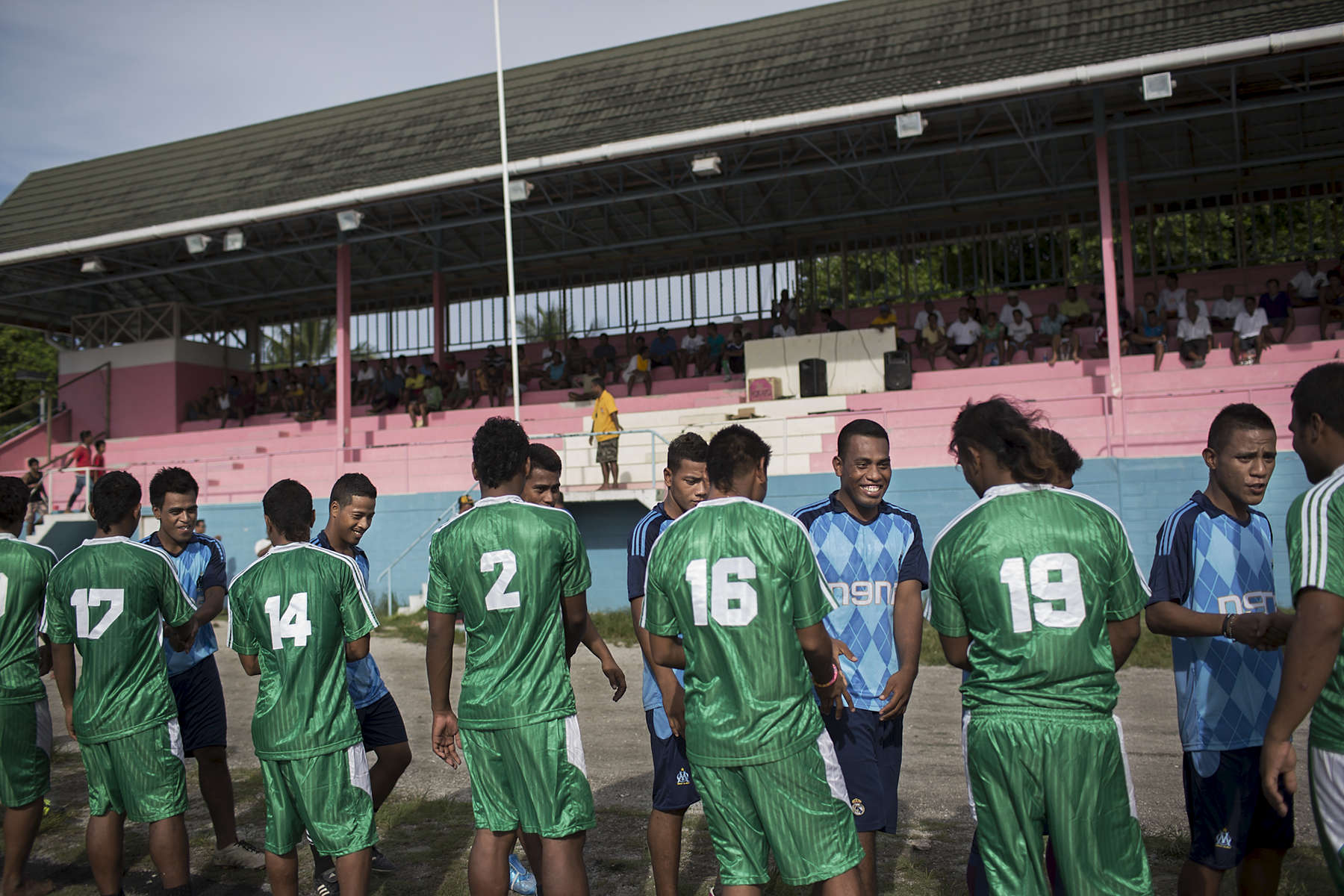 Soccer players shake hands before playing a game at the sports complex in Bairiki village.