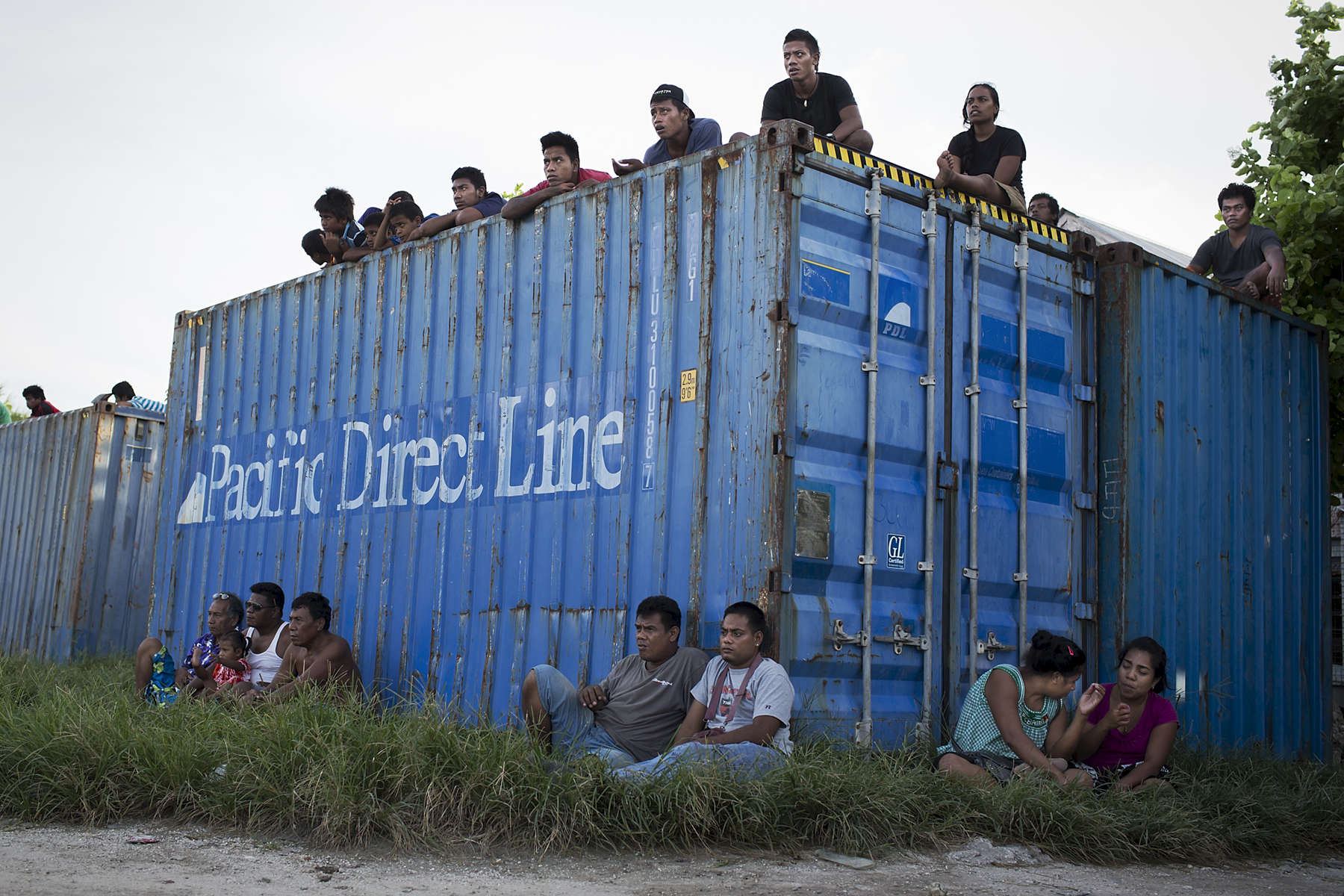 Onlookers watch a soccer game from atop of a shipping container  at the sports complex in Bairiki village, South Tarawa island, Kiribati.