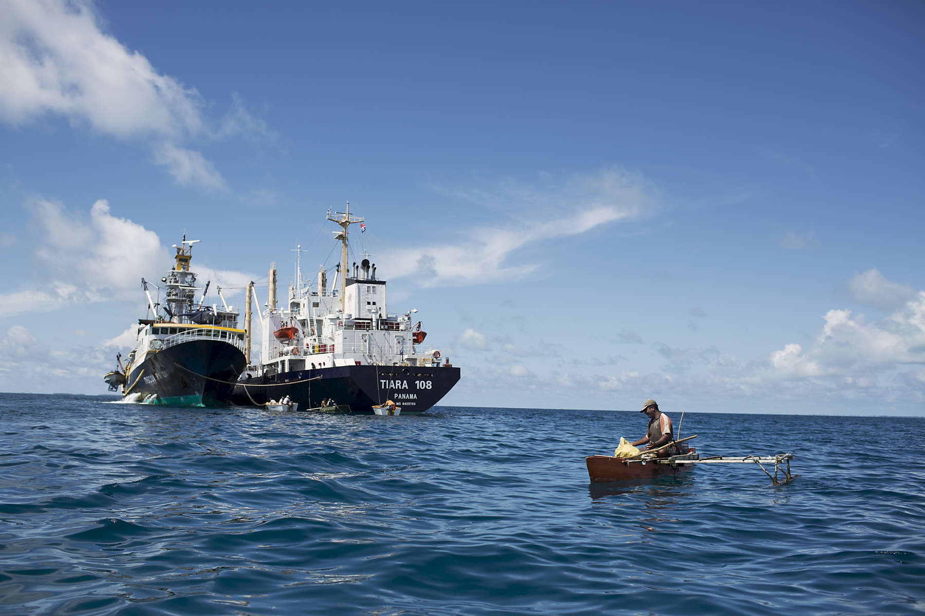 A fisherman on a small canoe fishes closeto an overseas fishing vessel. The Kiribati government have sold licenses to commercial fishing fleets from South Korea, Taiwan, Japan, United States and Spain. The most common fish caught by the commercial vessels are 54% big eye tuna, 34% yellow fin tuna, 2% marlin and 10% other (Source SPC).