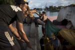 Men load drums of fuel onto a boat to be transported to small islands in Kiribati.