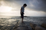 A boy plays on a flooded sea wall in Bairiki village, South Tarawa island of Kiribati.
