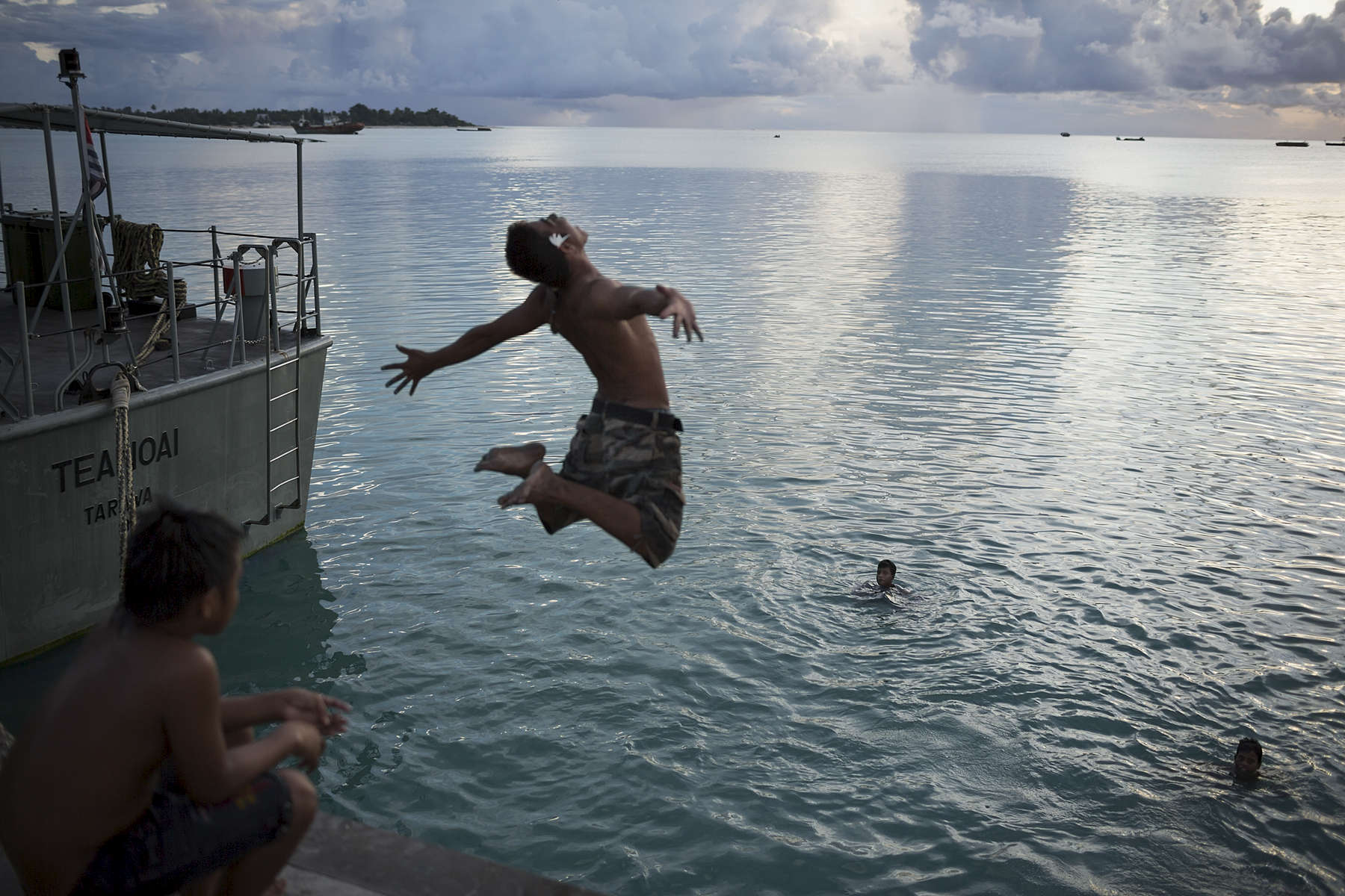 Local I-Kiribati youth jump off the Betio jetty in the late afternoon.