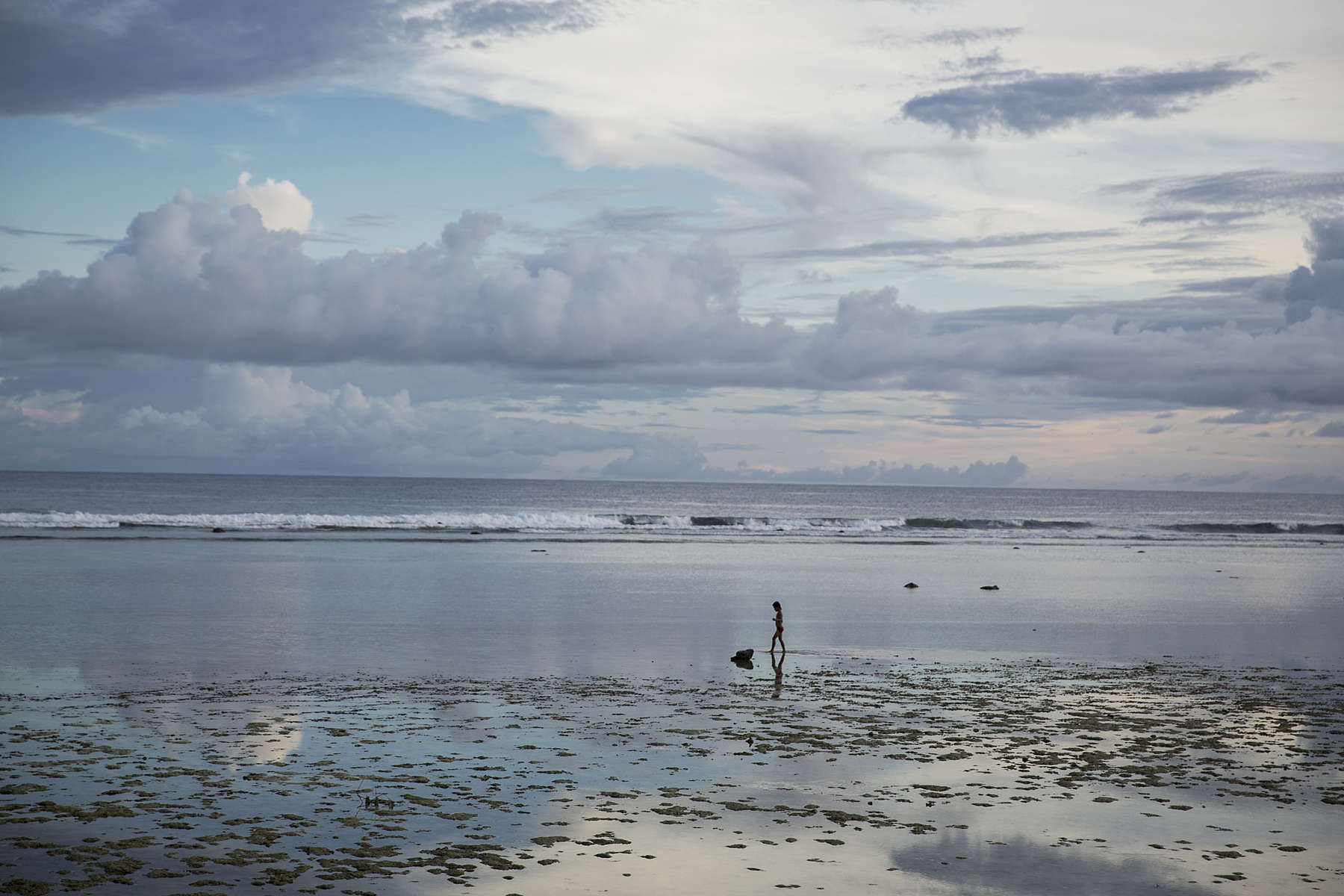 A child walks along the beach at sunset in n Bikenibeu village on South Tarawa island, Kiribati.