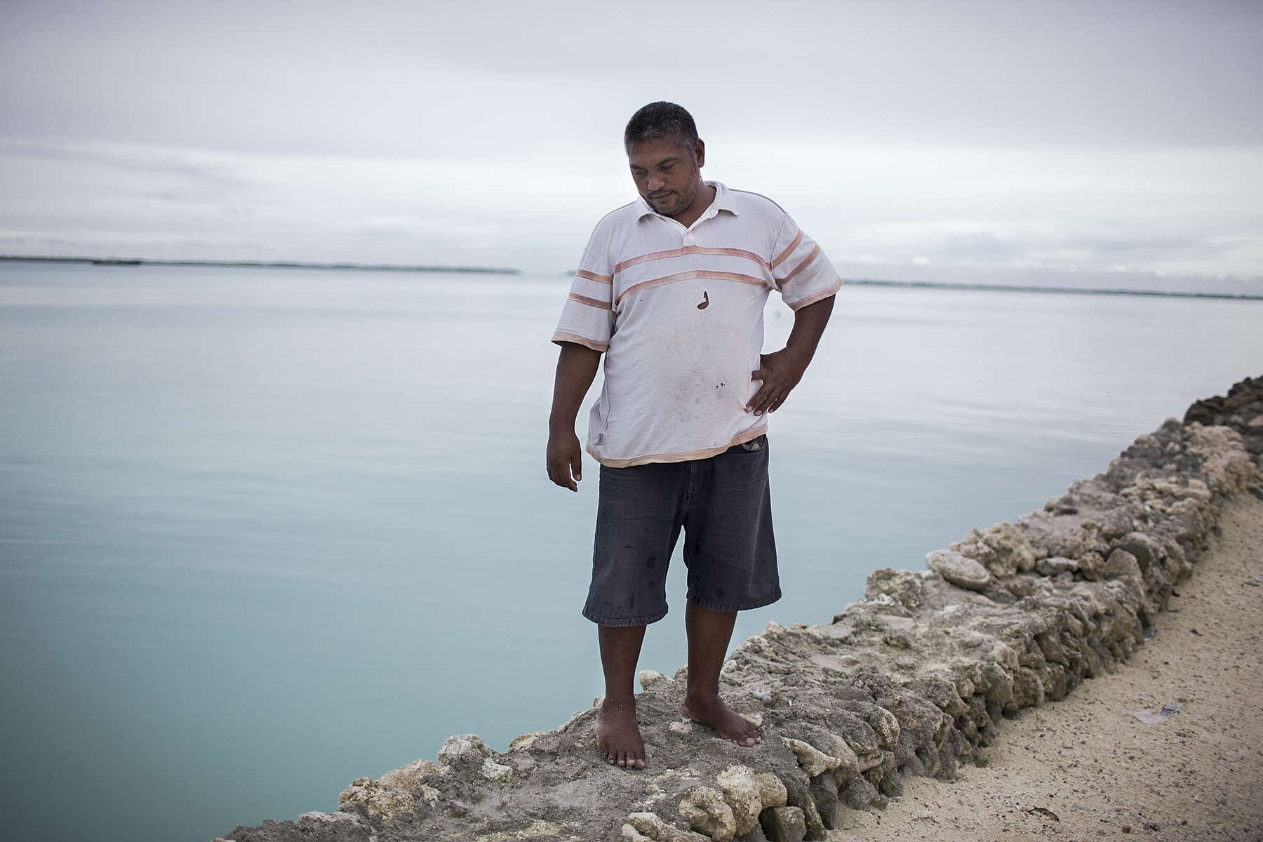 Moaniba Ratitaake, 40 years old, stands on the seawall he has built to protest his home.  Moaniba lives in Eita village on South Tarawa island, initially he could drive all the way to the house, but for the last 4-5 years much of the land remains underwater during hightide. Moaniba plans to build more sea walls around the land that reaches the ocean but he concedes this is only a short term fix for what will inevitably be uninhabitable land.