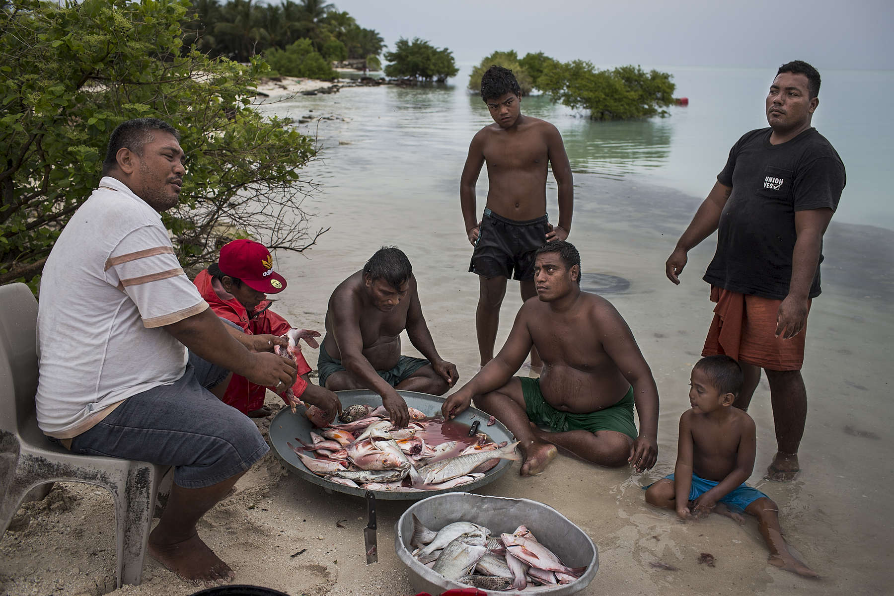 Moaniba Ratitaake (left), 40 years old has 7 children is a fisherman and supports his family by selling his catch. Moaniba lives in Eita village on South Tarawa island, Kiribati. Moaniba moved to Eita village to live on an area of land owned by his wives family once it was connected to water and electrcitiy. Initially he could drive all the way to the house, but for the last 4-5 years much of the land remains underwater during hightide. Moaniba plans to build more sea walls around the land that reaches the ocean but he concedes this is only a short term fix for what will inevitably be uninhabitable land.