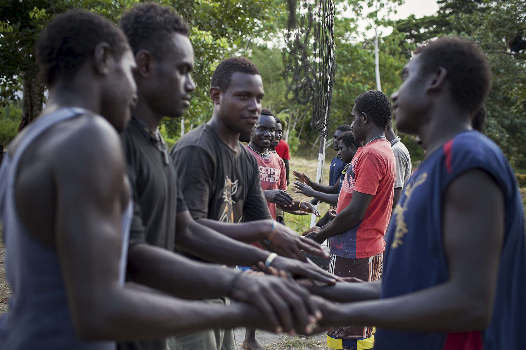 Young men attending Mabiri shake hands after finishing a game of volleyball.