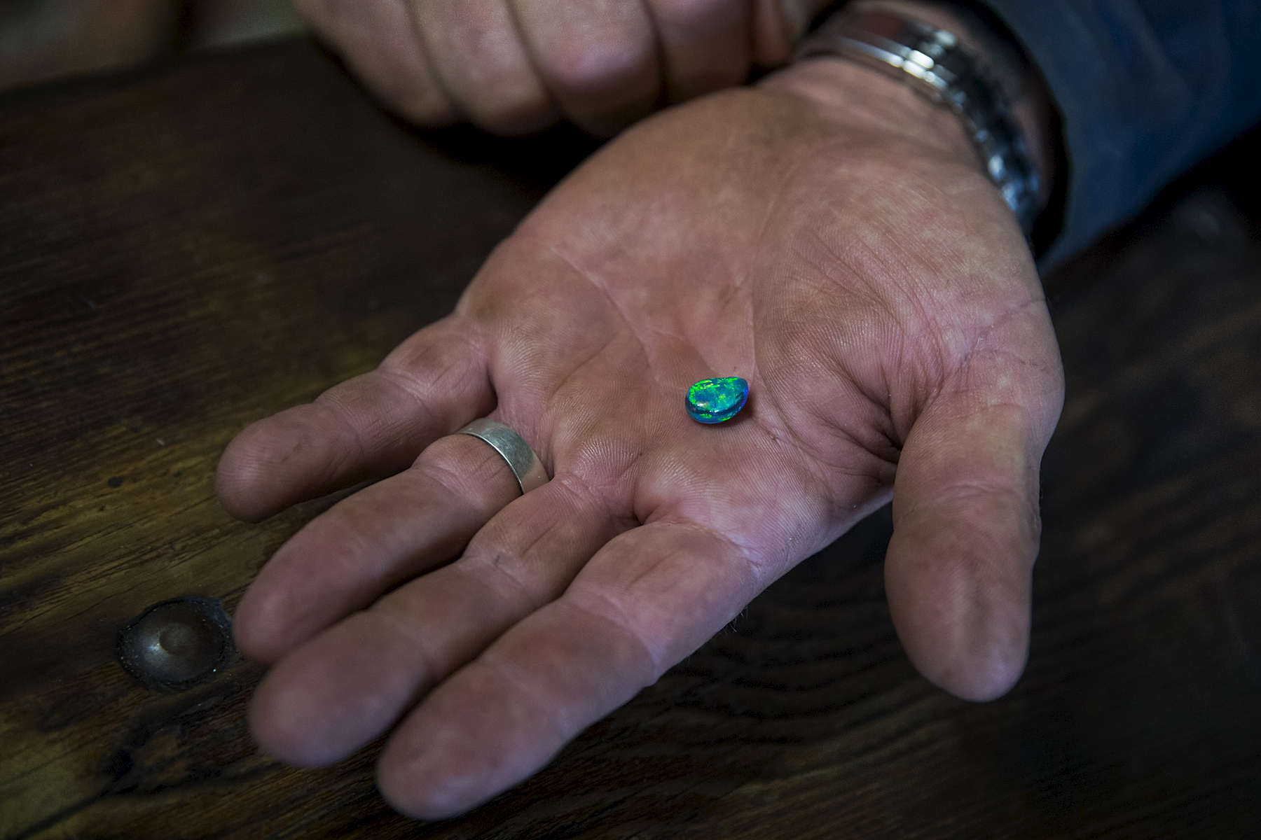 Mick Cooke holds an opal he has purchased for a friend. Mick sits around the table of his brothers Pete's home or 'man cave. Mick has lived in the remote opal mining town for the past 20 years while his brother Pete only permanently relocated to Lightning Ridge three years ago.  The brothers both show entrepreneurial abilities in the way they find business opportunitieis in the small town. Pete's 'man cave' contains a colourful array of items including two Harley Davidson motrobikes and an old sports car.  Conor Ashleigh for New York Times