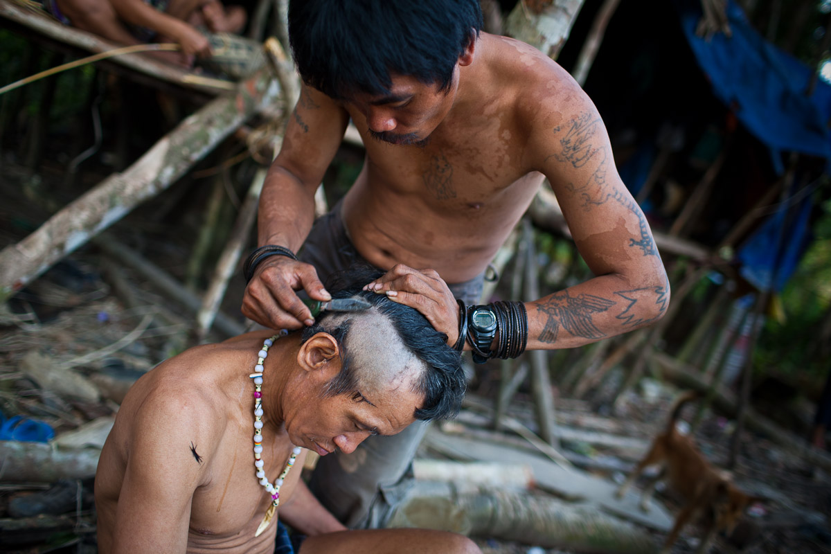 Bapa Sagung shaves the head of his father-in-law, Now Anit, around the family's camp.