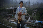 A man prepares to kill a chicken for dinner in Sekhersing in the Solo Khumbu region of Nepal. October 2013.