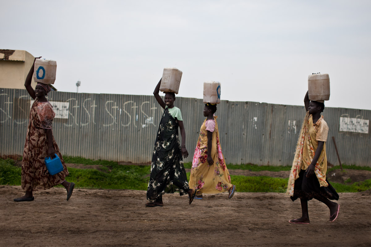 Local women in Malakal walk home after collecting water from the Nile River, which is a few kilometres walk each way, but a reality for most living in Malakal.