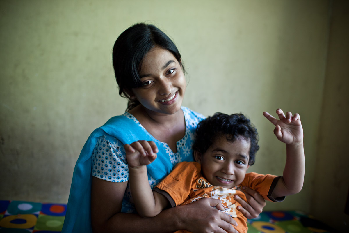 An older sister cuddles a younger boy inside their home in SOS Kolkata.