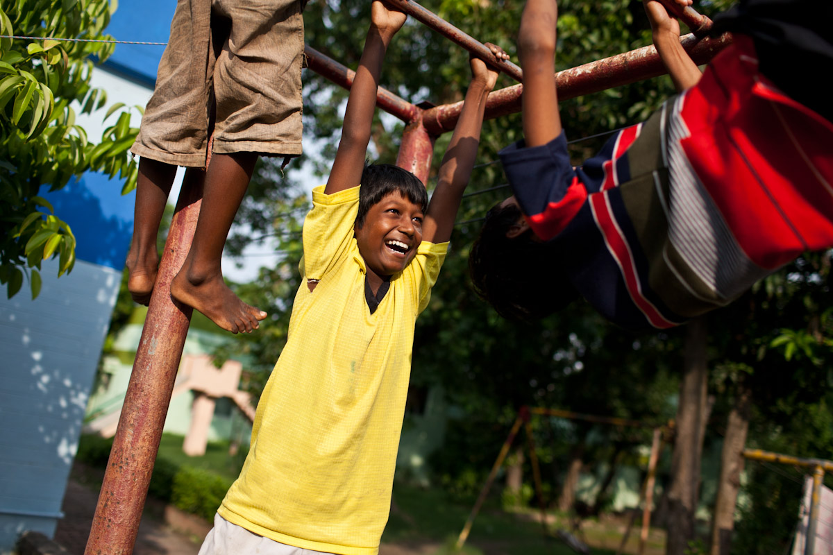 After school, boys play on the monkey bars as they wait for others to join and begin their daily game of football.