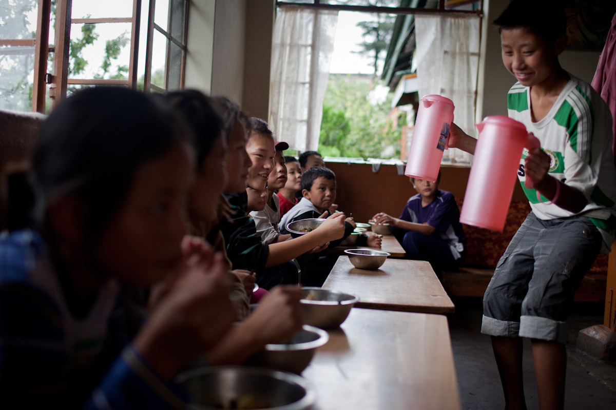 Children sit eating lunch together in the Tibetan Children's Village.