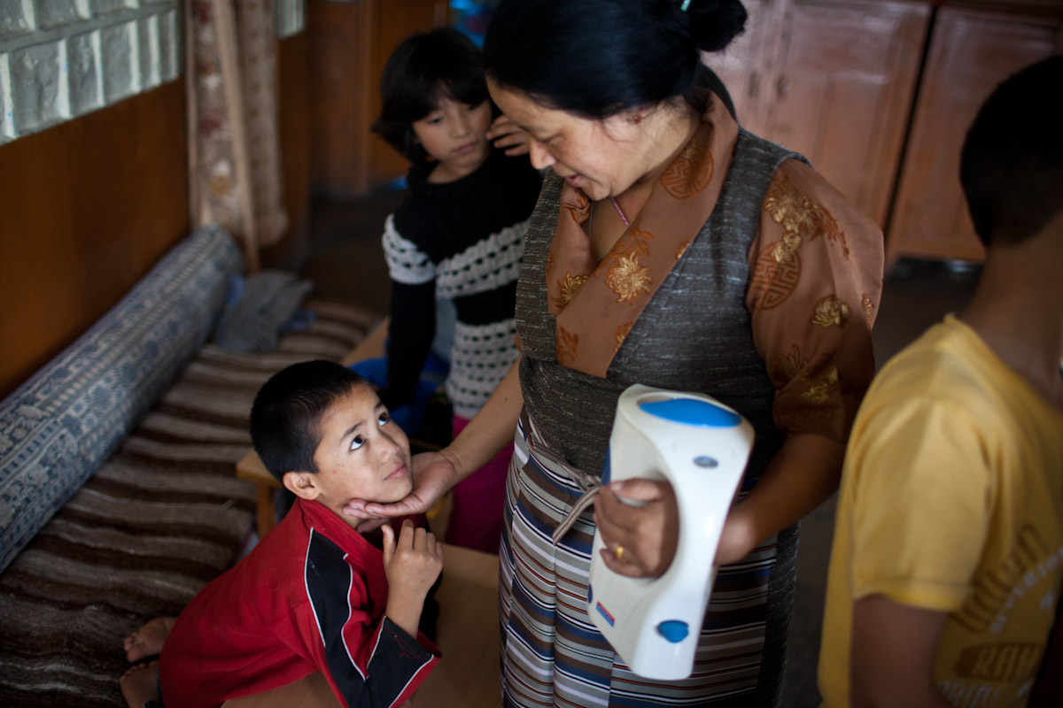 Housemother Sonam talks affectionately to Karma who arrived at the Tibetan Children's Village at the tender age of 3. Karma has a very strong bond with his housemother.