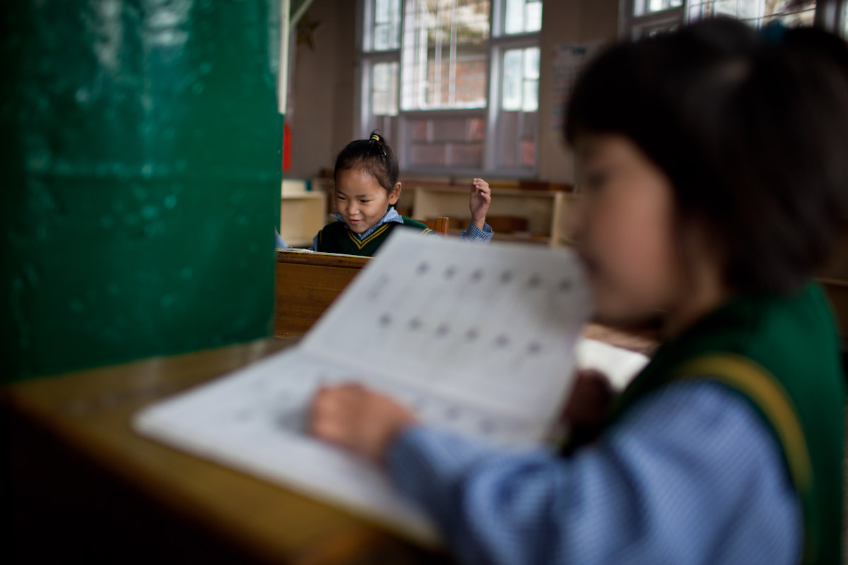 Two young girls read Tibetan books inside the kindergarten classroom at the Tibetan Children's Village.
