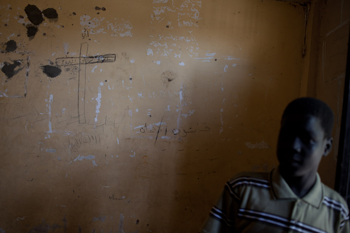 A boy stands in his old bedroom room which is now patched after damage from recent fighting in March.