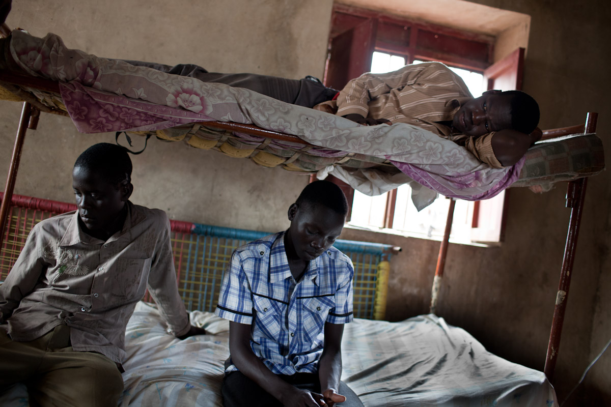 Young men sit inside the young men's house that is situated in the wider Malakal community, but still connected to the SOS Children's Village.