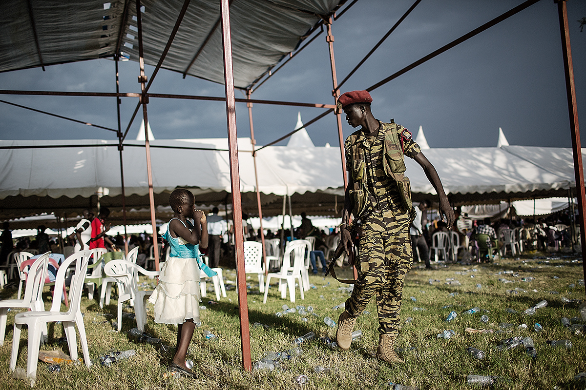 A soldier walks past a girl in Juba, South Sudan.
