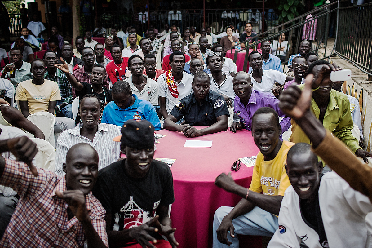 A crowd of predominantly young South Sudanese men crowd cheer on during a fight at the the International Kickboxing Challenge in Juba, South Sudan.
