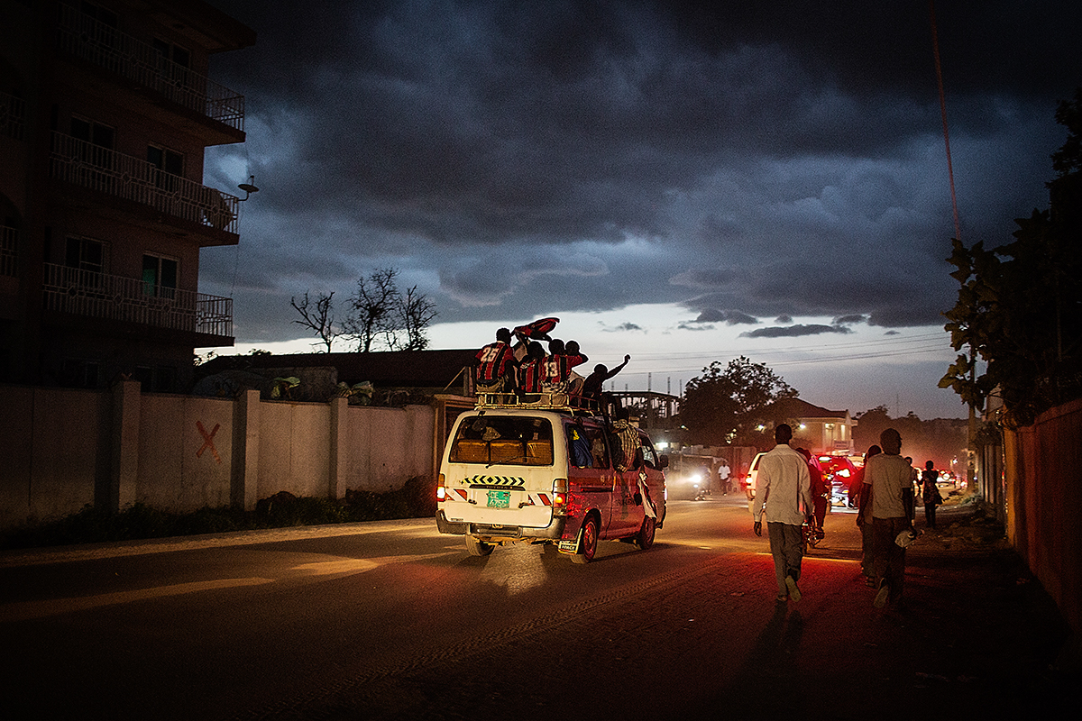 A football team aboard a mini van celebrate through Juba in the early evening.