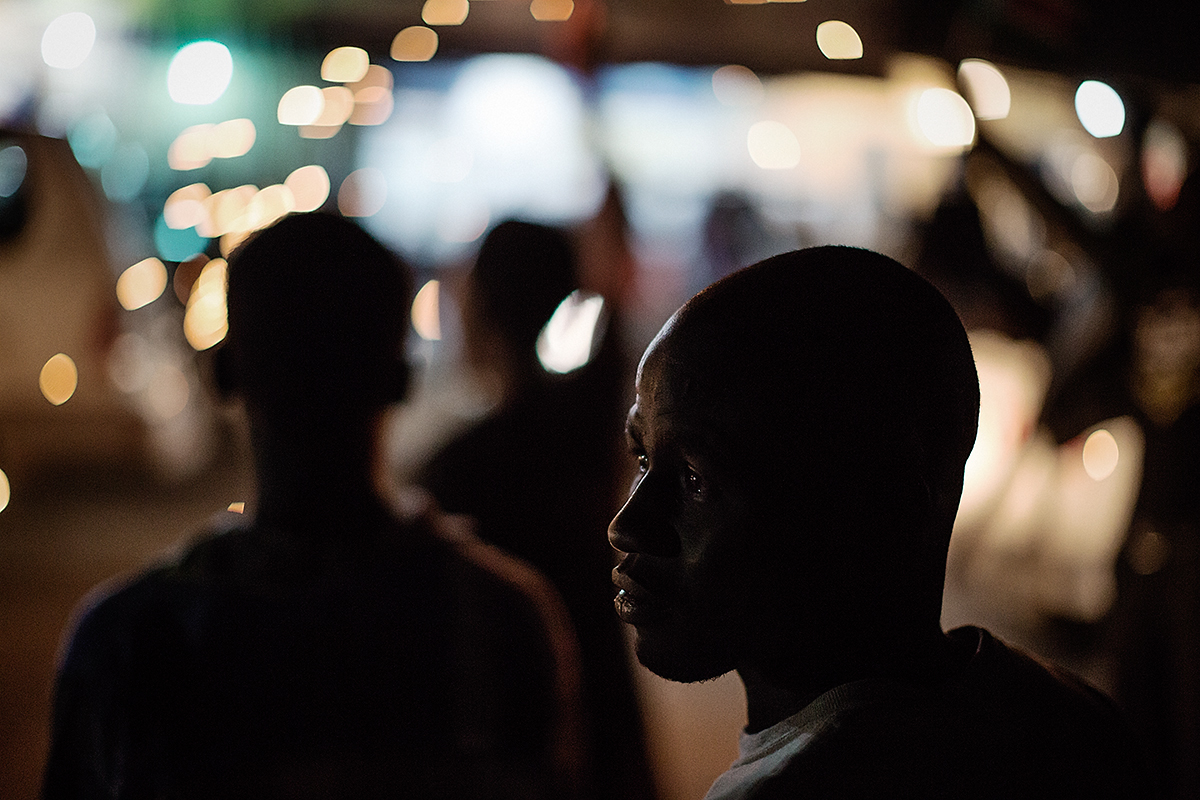A man stands on the streets and watches the wild independence anniversary celebrations which continue throughout the night.