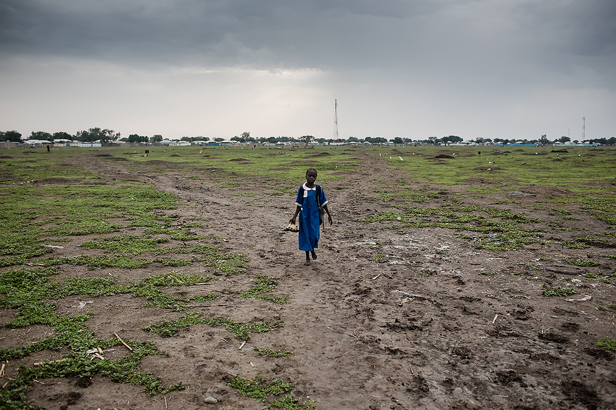 A young girl passes through a cemetery on her way to school in Malakal. Due to the high mortality rate and cost of funerals it is most common for graves to not be marked.