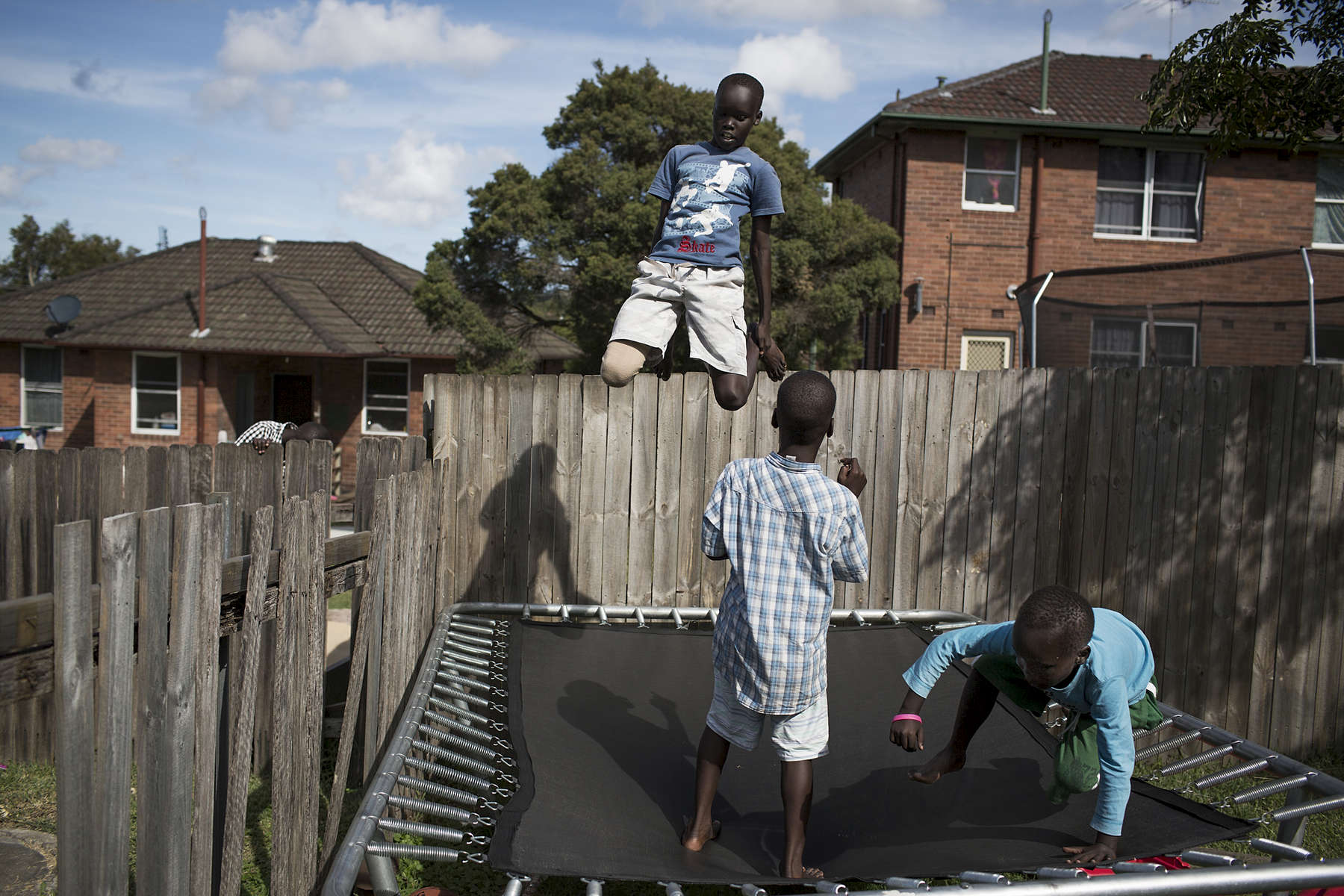 The Dong and Okumu families, both originally from South Sudan are from the Dinka and Acholi tribes respectively. Living in Newcastle, Australia, the families share a back fence and their children regularly play together. The families live in the suburb of Lambton which is also where the photographer grew up in, and where the Mayom family moved across the road in 2003.