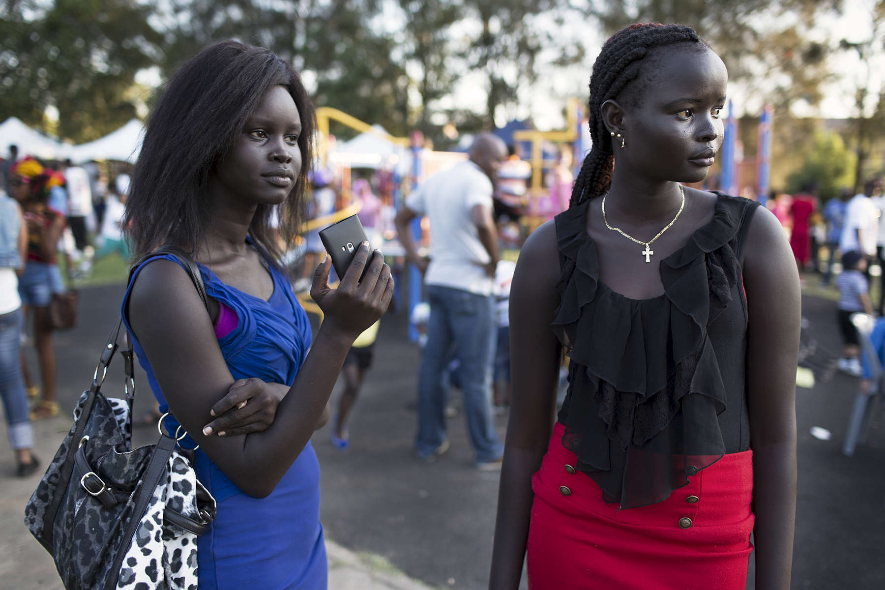 Ludia Ayak Manasseh (right) and a friend watch on as a group of young south Sudanese men walk past at Africultures Festival held in Western Sydney, 2013.