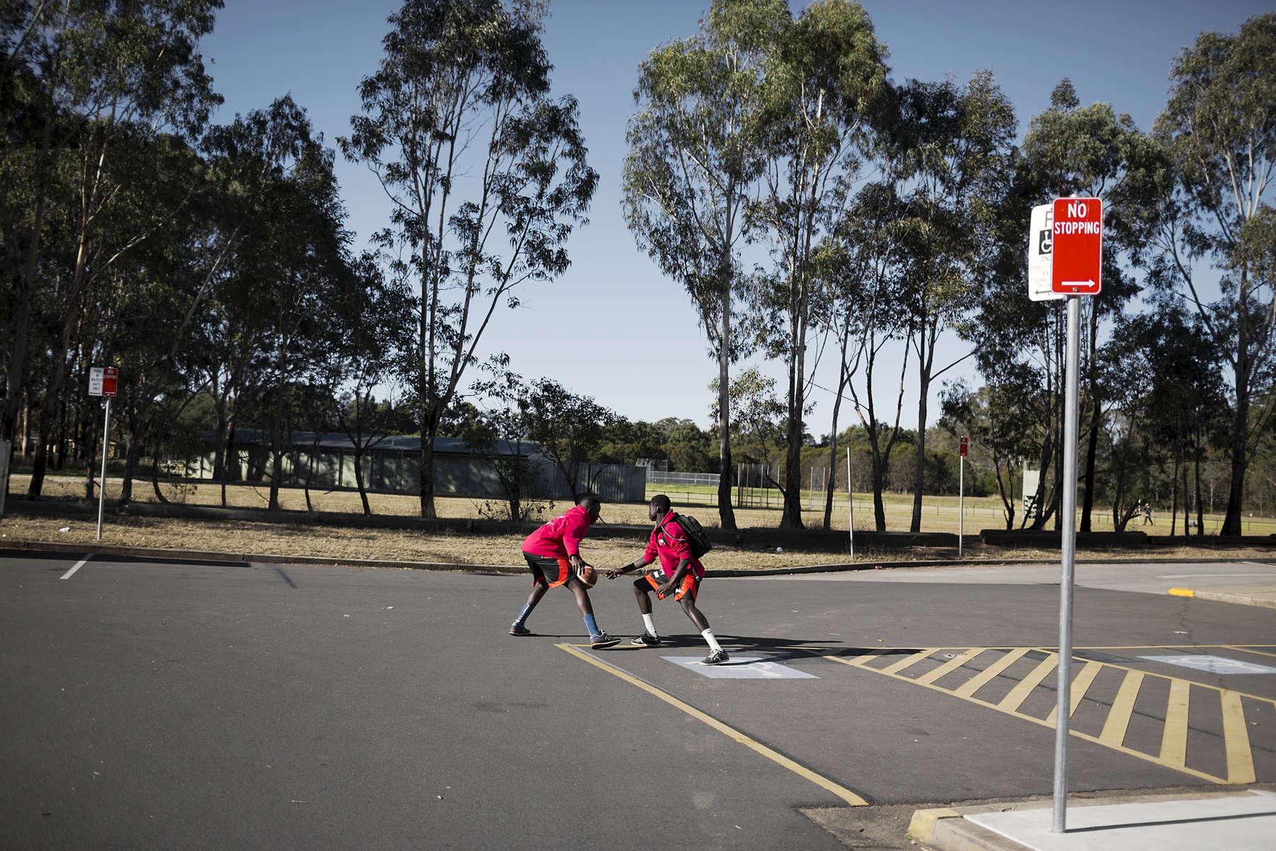 Young South Sudanese basketball players play one-on-one in the car park at the Penrith Basketball Stadium in Western Sydney. There are a number of young Australian South Sudanese basketball players currently at high schools and colleges in the United States including Thon Maker who is hoped will one day play in the NBA. Thon is attending high school at Orangeville District Secondary School and playing basketball for Canada's Athlete Institute.