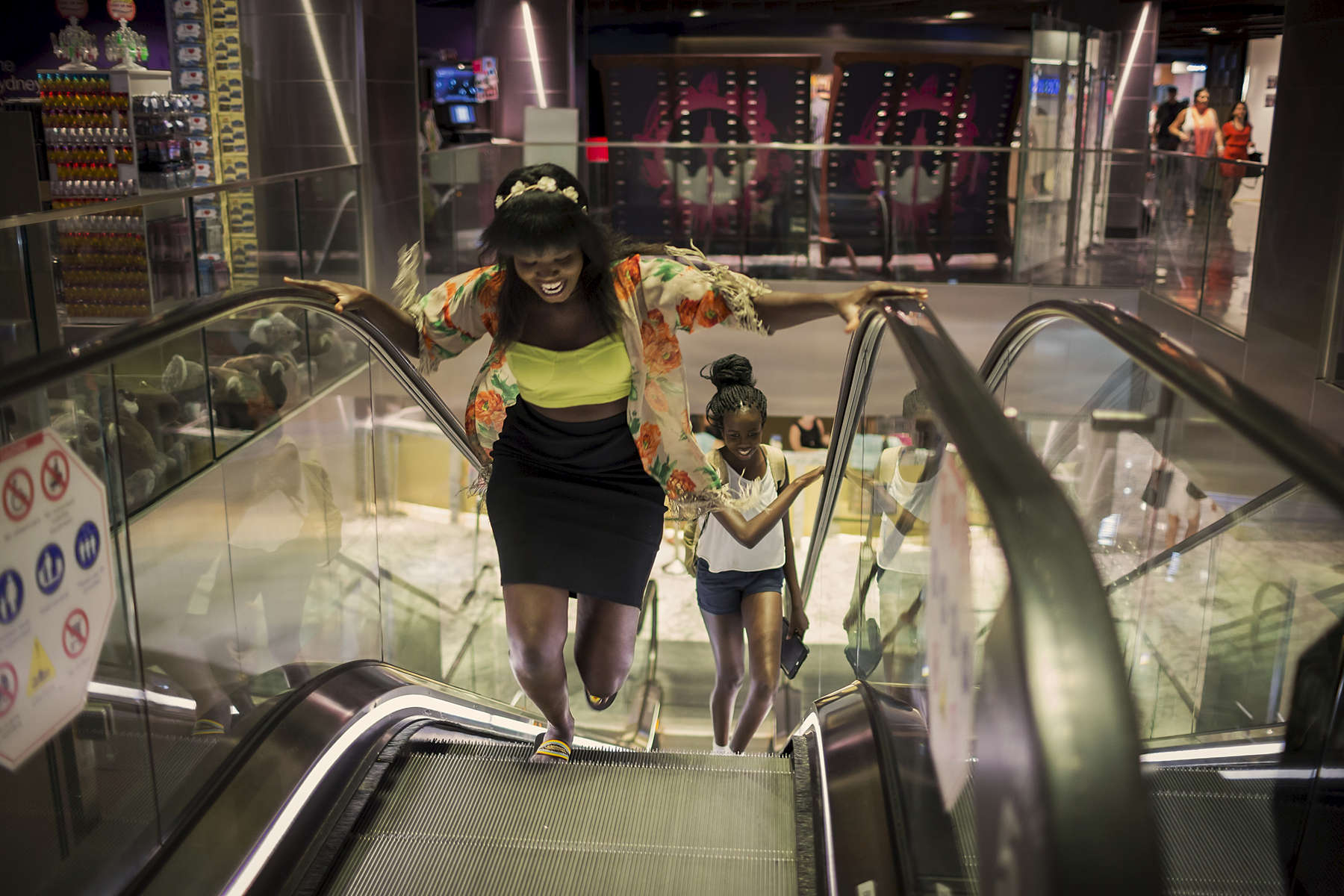 Achingol Mayom and her cousin Agudi run up a descending escalator in a Sydney shopping centre. When asked about the role of language in keeping South Sudanese culture alive, Achingol responded, 'at home and with my friends I speak a mixture of English and Dinka, I call it Dinklish'.  Aged 7 Achingol arrived in Australia in 2003 with her Mother and five siblings. A year later in 2004 the family moved across the road from the photographer and it is where they first met. Achingol was part of a group of young Australian South Sudanese who participated in a cell phone photography project the photographer crowd funded to run in January 2015.