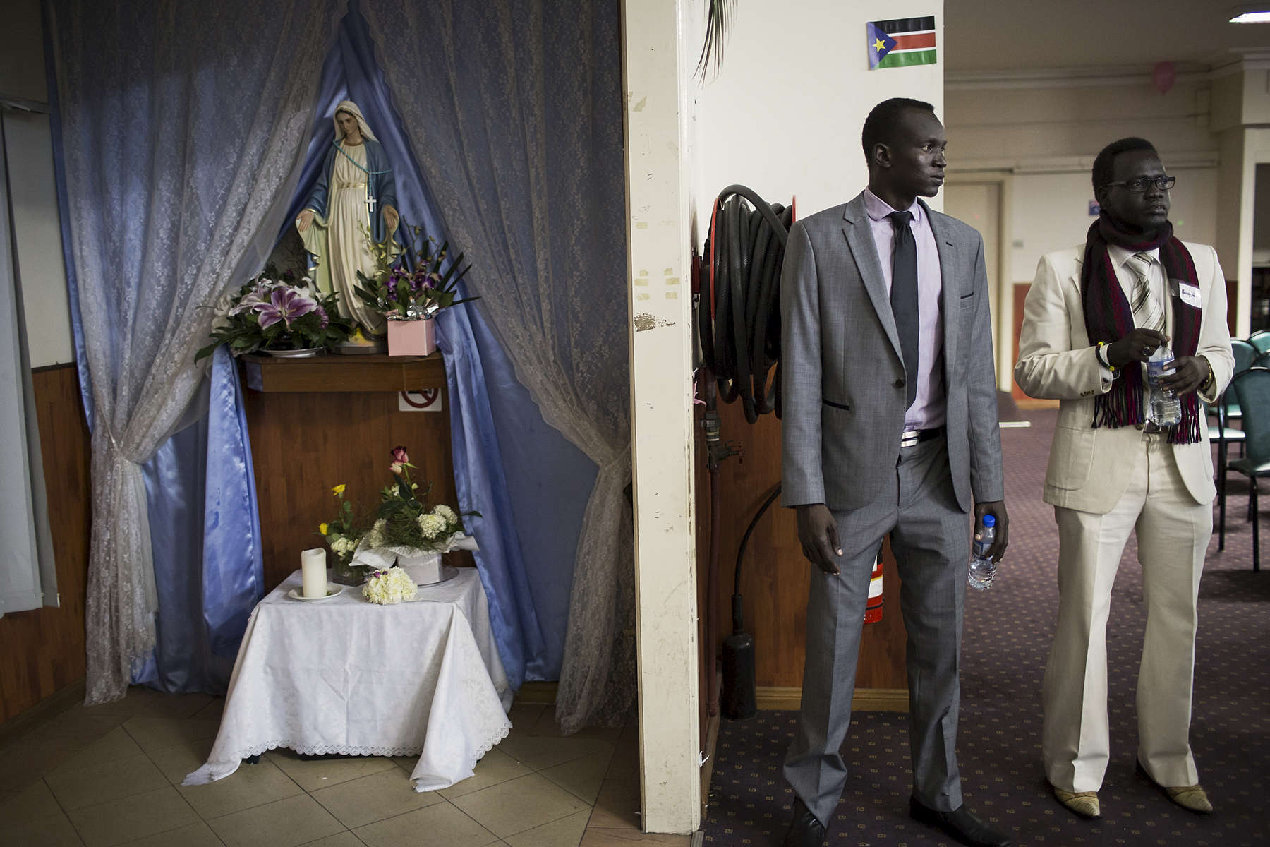 Two men stand at the door to welcome community members attending the 30th anniversary of the Sudan People's Liberation Army (SPLA) in Western Sydney in May 2013. The SPLA was founded as a guerrilla movement in 1983 and led by John Garang de Mabior until his death in 2005. Not long after South Sudan's independence in 2011, the world's newest nation was once again plunged into conflict after a falling out between Dinka President Kiir and Nuer former Vice-President Machar turned rebel leader. After a 15-month civil war that has killed thousands, many hope the most recent peace deal can last.
