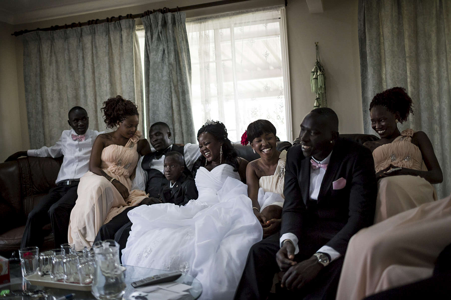 In December 2013 bride and groom Achol (centre) and Marial (left of bride) along with their bridal party take a brief rest after the wedding ceremony and before the reception. Weddings are an important part of adulthood and cultural life for Australia's South Sudanese community. Amongst the Dinka and Nuer communities in Australia it is still very common for a bride price to be paid by the groom and his family to the wives family. A separate wedding the photographer documented in early 2015 $65,000 AUD was agreed upon by the families to be paid as the bride price.
