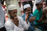 Men pray on the street outside Bashundhara City a large shopping complex in Dhaka. On Friday Jumu'ah prayer occurs just after midday and most men take part.