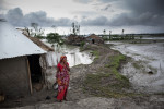 In Jaliakhali village a women stands outside her home which has been rebuilt atop an embankment, after it was destroyed during cyclone Aila in 2009.