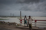 Men stand along a roadside in Ashulia with flooded brick kilns behind them.
