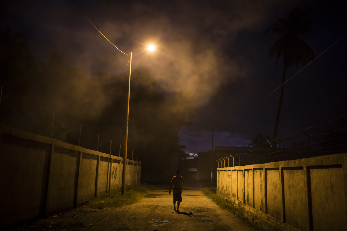 A man walks through the streets of Dili after leaving a small backyard futu manu ring in the Bidau neighbourhood.