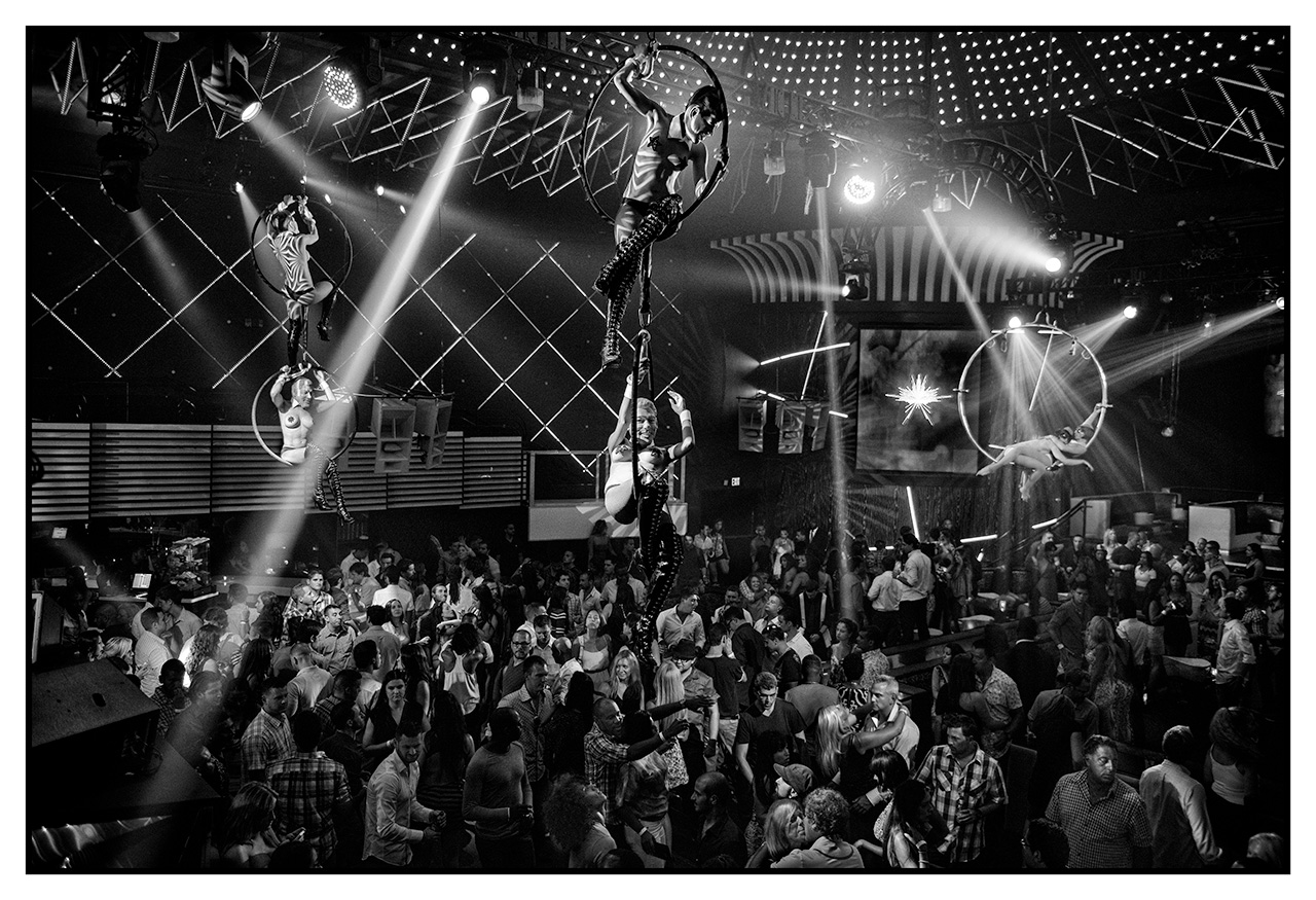 Entertainers perform high over head as the crowd dances at one of the worlds finest nightclubs in Miami Beach, FL.