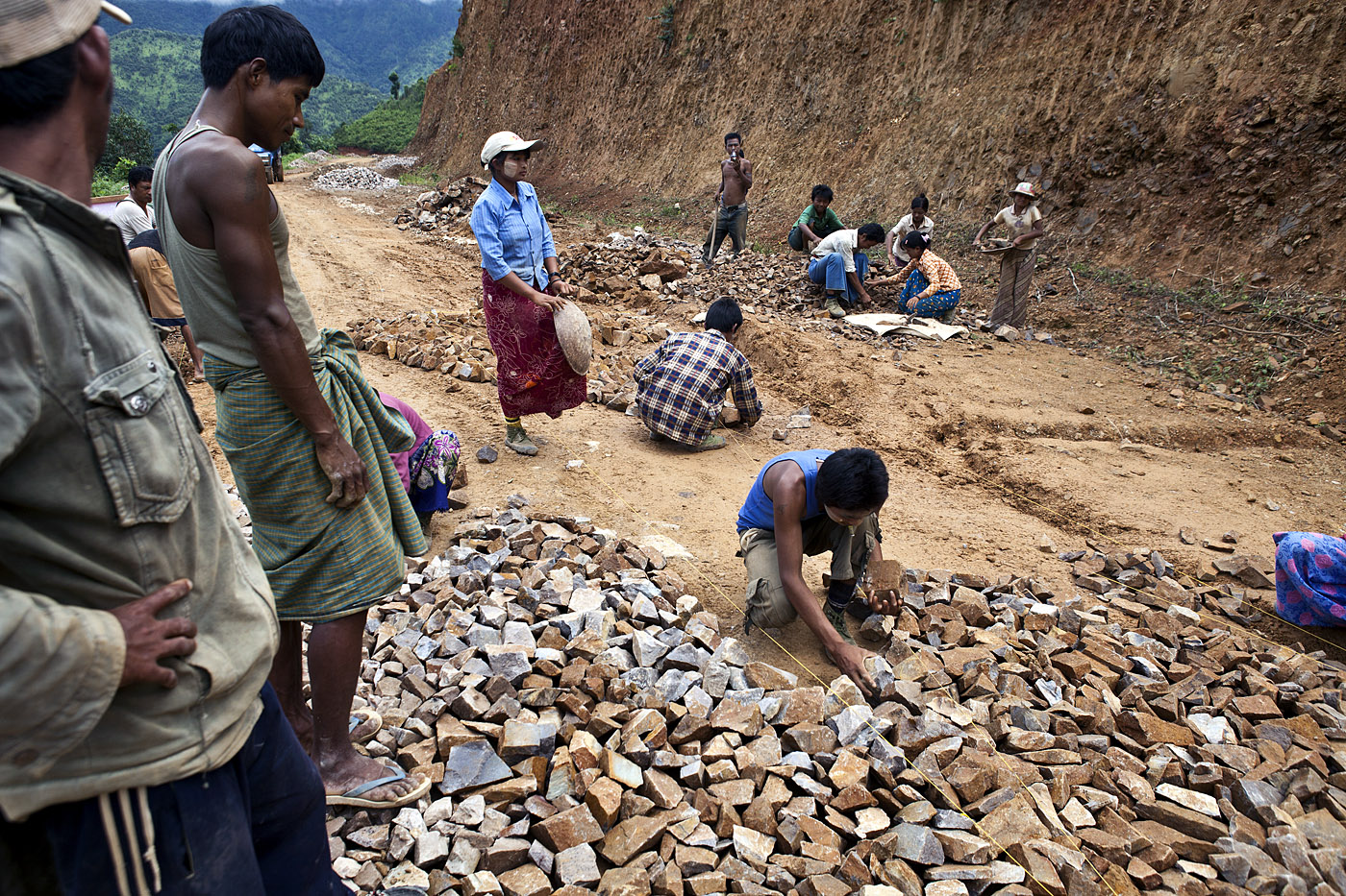 Laborers lay a base course of rough stone to the Namshan – Hsipaw road.  The road is the main artery for transporting tea south to the larger markets of Mandalay and Yangon.  Because the road is unpaved the majority of way, the short journey can easily take six hours in the dry season and much longer during the rainy season, when it becomes prone to landslides.