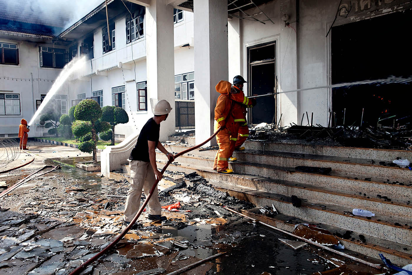 Udon Thani, Thailand. Firefighters spray water on a government office Wednesday, May 19, 2010, following a riot by anti-government protesters. The attack on the Thai government office came after TV showed reports of the crackdown on Red Shirt protesters in Bangkok.