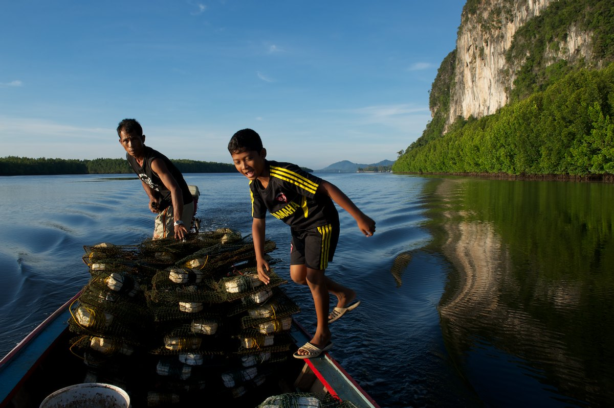 Bang Dii and his son Waa prepare to drop crab traps within the coastal mangrove ecosystem of Hat Chao Mai National Marine Reserve.