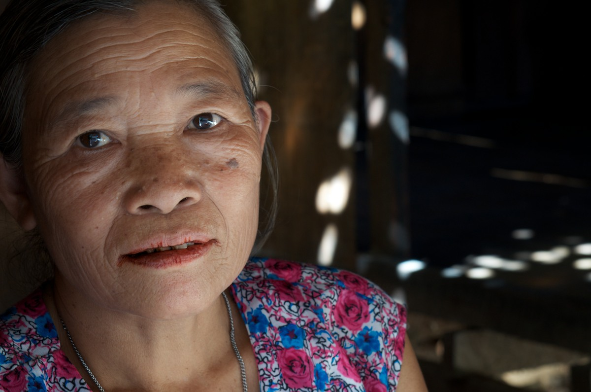 A portrait of a Karen woman in her home, who's lips are stained from chewing local beetle nut.