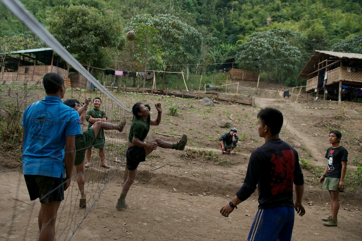 Medical staff and students of the Free Burma Ranger's Jungle School of Medicine Kathoolei play a competitive game of Takraw in camp. Takraw is a skill ball game that requires each team to pass the ball over the net and within the court boundaries using only their heads and feet, touching the ball a maximum of three times on each play. The team who fails this, gives up a point and each game is played to 15 points. (From left to right) The camps outpatient clinic, classroom and women's dormitory line the hillside.