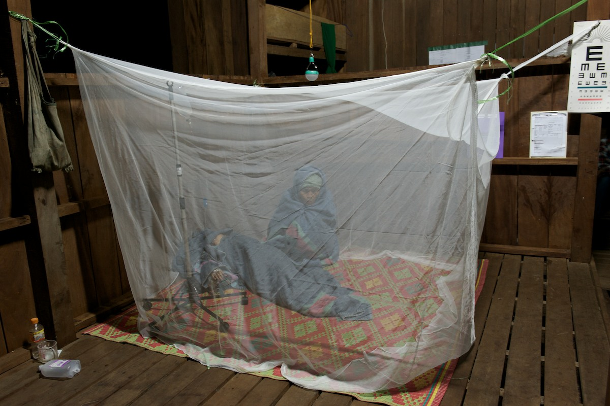 A mother watches over her young daughter who has been diagnosed with severe malaria at the Free Burma Ranger Jungle School of Medicine Kawthoolei in-patient clinic.