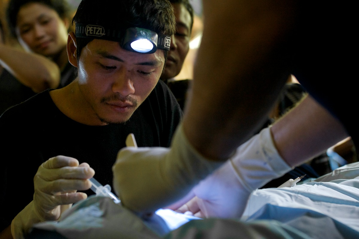 Toh, a medic with the Free Burma Rangers and staff member of the Jungle School of Medicine Kawthoolei, performs a minor surgery on a patient's mouth as younger medical students watch and learn.