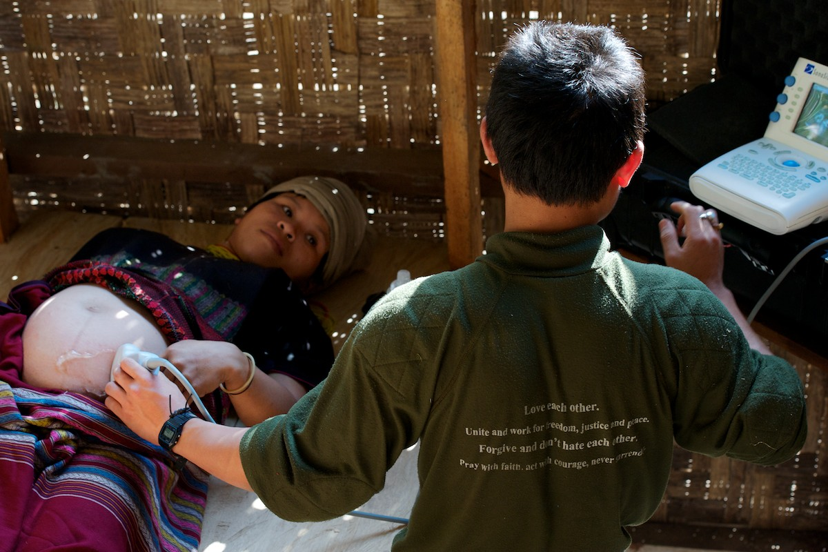 Saw Hsa Htoo, medical student at the Free Burma Ranger's Jungle School of Medicine, provides an ultrasound examination on an expecting mother who had never seen or been treated with ultrasound during her previous 3 pregnancies.