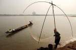 An elderly women net fishes on the bank of the Mekong River as her husband returns with nets he had set the previous night.