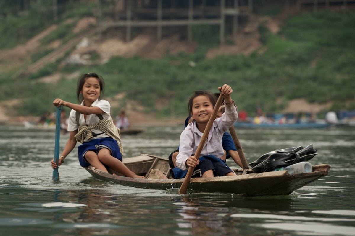 A group of children paddle to school on the confluence of the Nam Ou and Mekong rivers, near Pak Ou, Laos.
