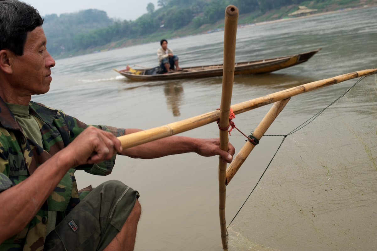 A fisherman uses a traditional net fishing technique to fish along the banks of the Mekong River. In the background a {quote}slow boat{quote} navigates locals and tourists upstream and downstream, stopping at tourist sites and villages.