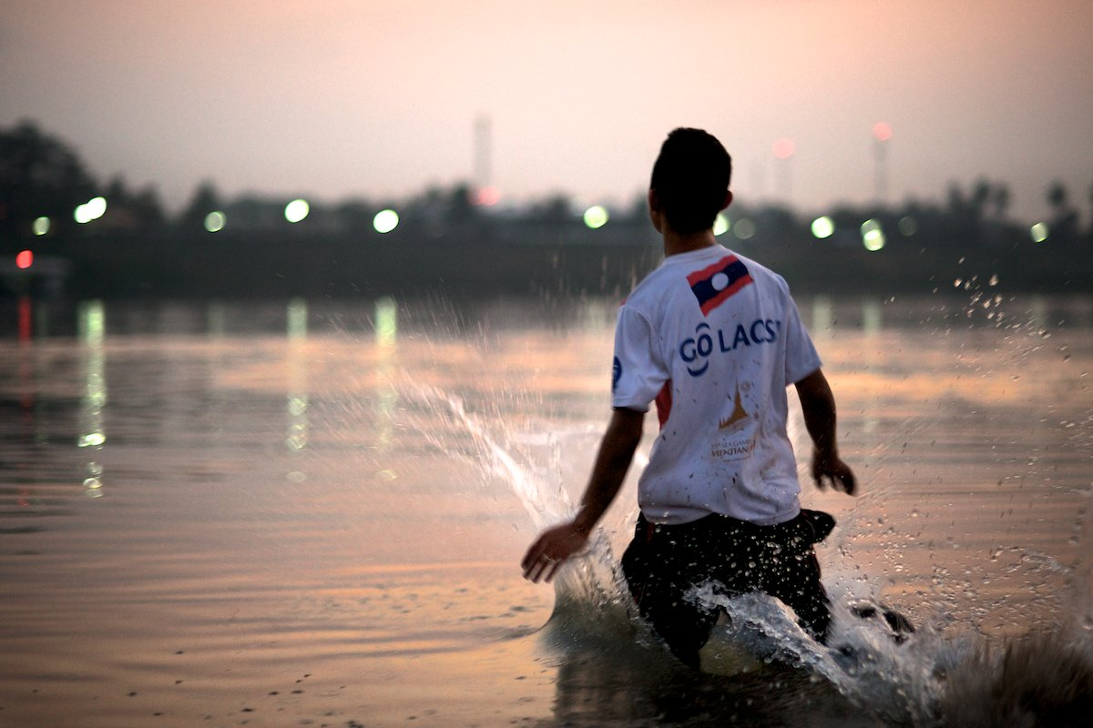 A young boy plays in the Mekong River, cooling off after a hot day during the dry season.
